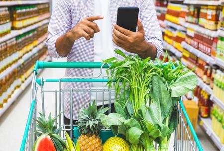 Young man shopping at supermarket.