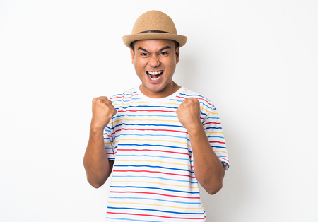 Happy young asian man celebrates with two hand in the air on isolate white background.