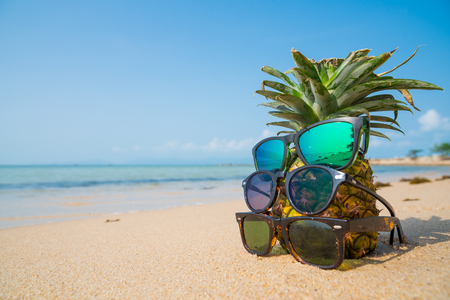 Pineapple with sunglasses on tropical beach background. 版權商用圖片 - 122572162