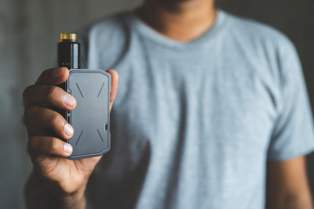 Young man holding electronic cigarette.