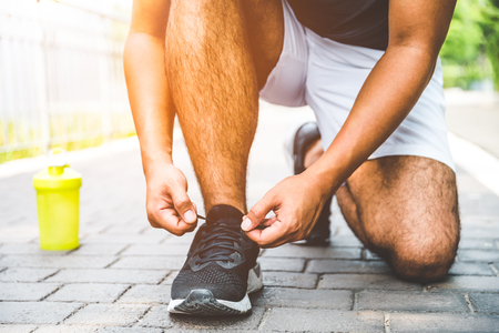 Runner young man tying shoelace getting ready for race on run track. Healthy fitness, workout, sport, lifestyle and sport concepts.