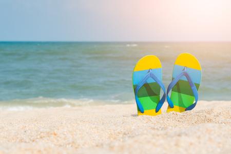 Beach sandals on the sandy coast for background summer concept. Reklamní fotografie