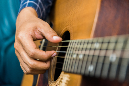 Close up left hand of guitar player