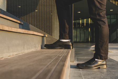 Businessman legs walking up the stairs