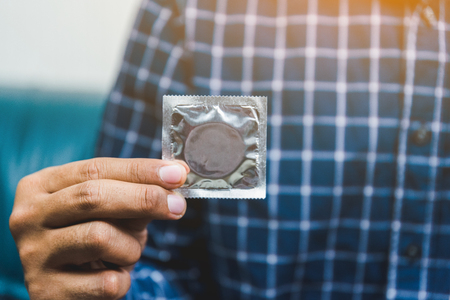 Male hand holding Condom. Safe concept.