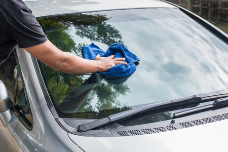 Hand man cleaning car with microfiber cloth