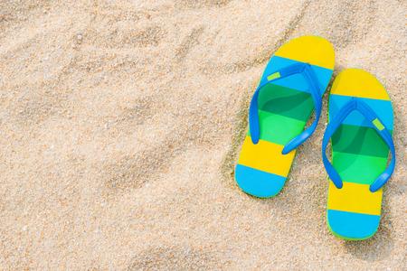 Beach sandals on the sandy coast. Summer concept with copy space. Reklamní fotografie