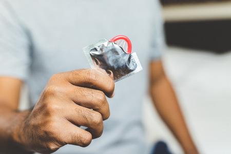 Male hand holding Condom. Safe sex concept. 版權商用圖片