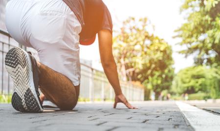 Athlete man in running start pose