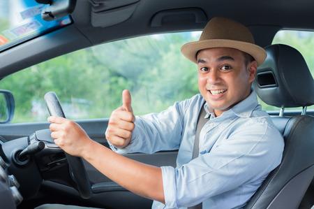 Giovane uomo asiatico che mostra i pollici in su mentre guida l'auto con lo spazio della copia. Archivio Fotografico