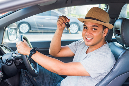 Young asian man holding key while sitting in new car