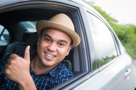 Jonge aziatische man duimen opdagen tijdens het autorijden met kopieerruimte.