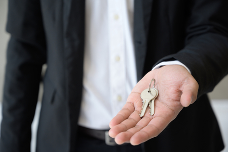 Close up business hand holding key in house.