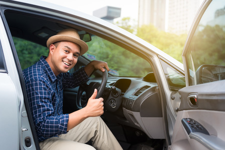 Young handsome asian man showing thumb up while driving car to travel.