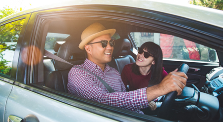 Funny moment couple asian man and woman sitting in car. Enjoying travel concept. Standard-Bild