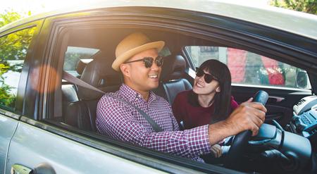 Momento divertido pareja hombre asiático y mujer sentada en el coche. Disfrutando del concepto de viaje. Foto de archivo