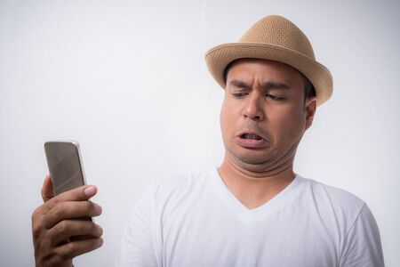 Angry Asian man looking smartphone