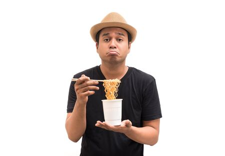 Young man boring to eat instant noodles Stock Photo