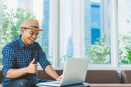 Young casual Asian businessman using laptop computer notebook for work.