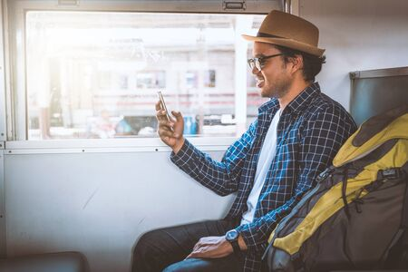 Young tourist man using smartphone while sitting in the train Banco de Imagens