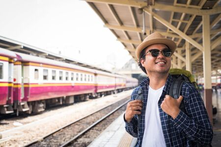Traveler man standing and waits train on railway platform