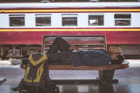 Young traveler sleeping in train station. Banco de Imagens