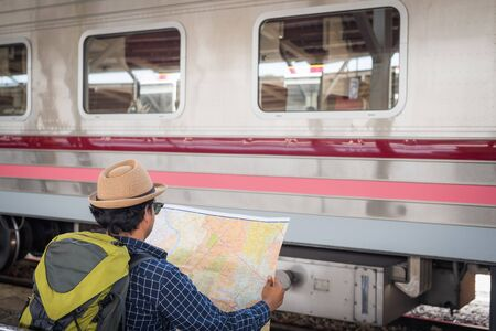 Young asian man open the map for travel at train station