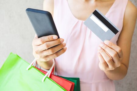 Close up of woman hand holding shopping bags, smartphone and credit card.