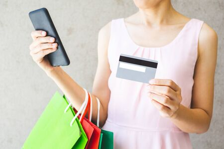 Close up of woman hand holding shopping bags ,smartphone and credit card.