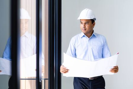 Young asian engineer or architects holding layout plan of building.