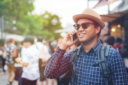 Traveling man using smartphone at Chatuchak Market in Bangkok Thailand.
