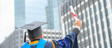 Happy graduate. Happy Asian man in graduation gowns holding diploma in hand on urban city background. 写真素材 - 131898115