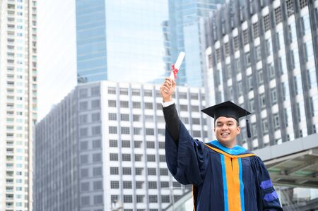 Happy graduate. Happy Asian man in graduation gowns holding diploma in hand on urban city background. Stok Fotoğraf