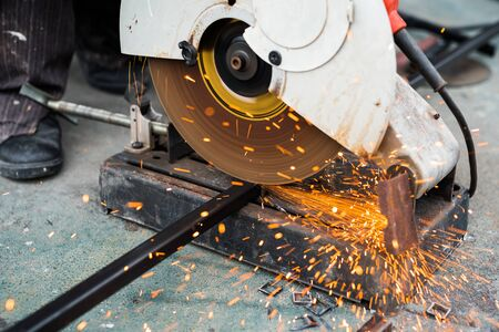 Close up worker using machine cutting steel