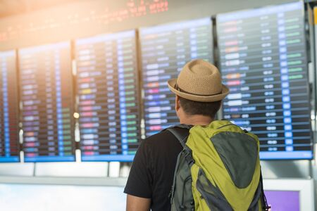 Traveler man looking at flight timetable in airport.