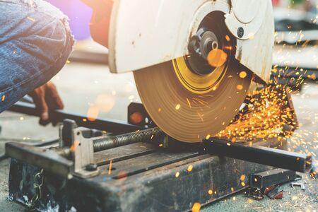 Close up worker using machine cutting steel