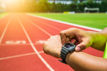 Athlete checking his watch on running track