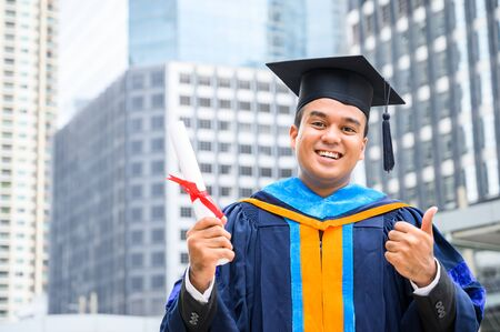 Happy graduate. Happy Asain man in graduation gowns holding diploma in hand on urban city background.
