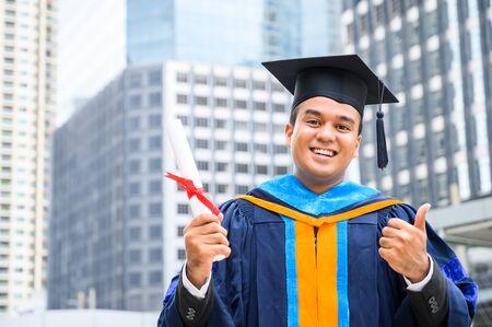 Heureux diplômé. Heureux homme Asain en robes de graduation tenant un diplôme en main sur fond de ville urbaine.