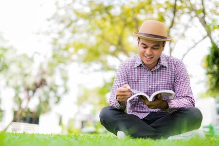 Young asian man reading a book study Concept.