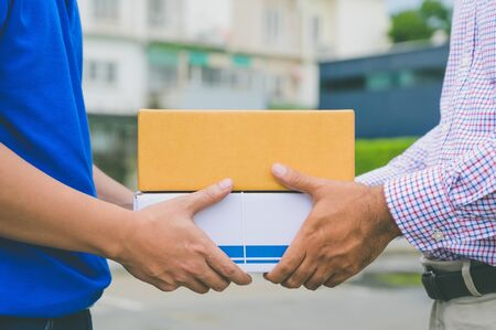 Hand accepting a delivery of boxes from delivery man.