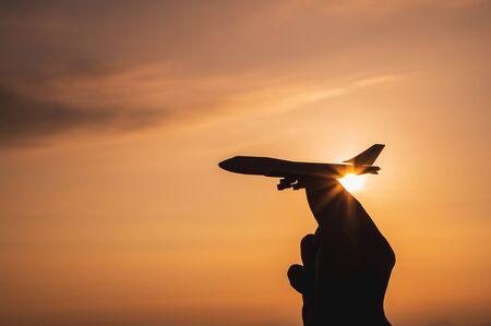 おもちゃの飛行機を持つ手夕日の光で空に行く