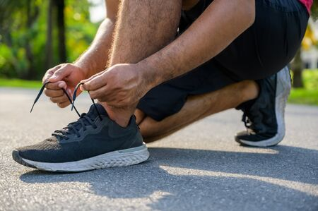Running man tying shoelaces. Fitness and sport healthy lifestyle concept.