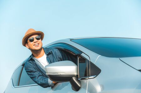 Young handsome asian man driving car to travel on his holiday vacation time with beautiful blue sky. Banque d'images