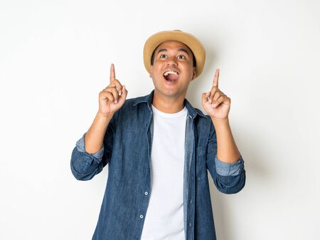 Happy Asian man, aged 30, wears a hat, wears a jean shirt, stands, pointing, to an empty space. Stock Photo