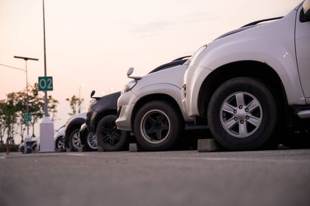 Many cars are parked in a large parking lot. Arranged in a long line Was the time when the sun was setting