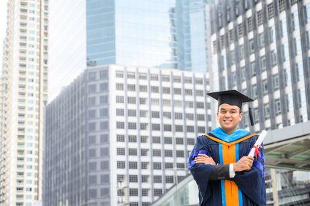 毕业快乐。在城市背景下,快乐的阿塞恩男人穿着毕业礼服拿着文凭。