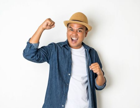 Asian men aged around 30 wearing hats and jeans feeling happy celebrate with two hand stretch on white background. Stock Photo