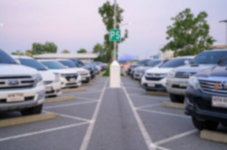 Abstract Blurred image of Many cars are parked in a large parking lot. Arranged in a long line Was the time when the sun was setting