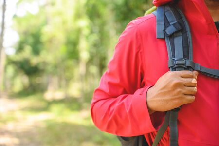 Hipster Hikers wear red raincoats, green backpacks, travel into the deep forest.